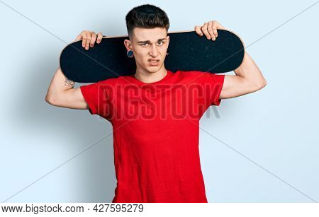 Young caucasian boy with ears dilation holding skate over shoulders clueless and confused expression. doubt concept.