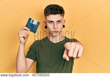 Young caucasian boy with ears dilation holding floppy disk pointing with finger to the camera and to you, confident gesture looking serious