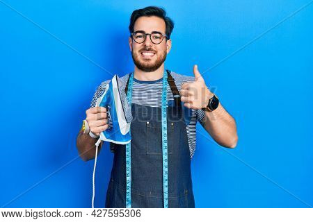 Handsome caucasian man with beard dressmaker designer wearing atelier apron holding iron smiling happy and positive, thumb up doing excellent and approval sign