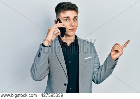 Young caucasian boy with ears dilation having conversation talking on the smartphone smiling happy pointing with hand and finger to the side
