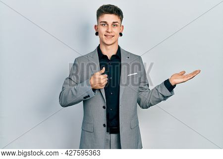 Young caucasian boy with ears dilation wearing business jacket showing palm hand and doing ok gesture with thumbs up, smiling happy and cheerful