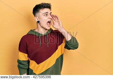 Young caucasian boy with ears dilation wearing casual sweatshirt shouting and screaming loud to side with hand on mouth. communication concept.