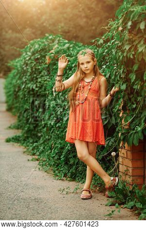 Romantic hippie style. Full length portrait of a cute girl child dressed in hippie style stands by a green hedge.