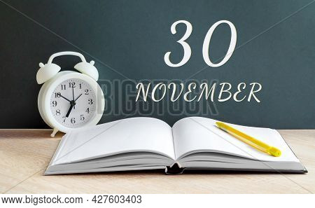 November 30. 30-th Day Of The Month, Calendar Date.a White Alarm Clock, An Open Notebook With Blank