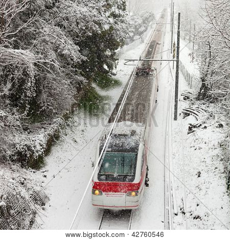 Passenger train moving along snow track