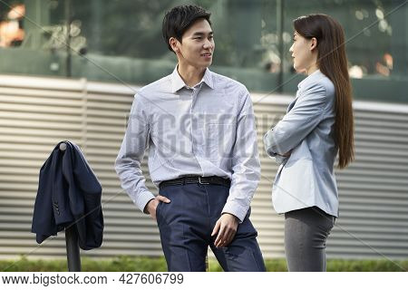 Two Young Asian Business People Standing On Street Chatting Talking Conversing