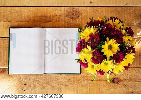 Composition Of Flowers In A Tea Mug And A Notebook On A Wooden Table In The Morning In Summer Or Spr