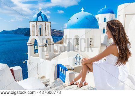 Luxury travel Greece vacation Asian elegant woman on honeymoon enjoying view of blue sea and three domes in white dress. Summer holidays on Oia, Santorini greek island, Europe.