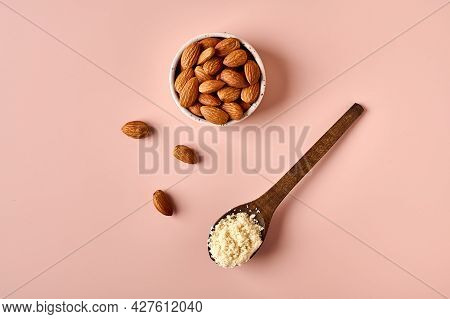 Almond Flour In Wooden Brown Spoon And Nut Kernels On Pink Powder Background. Top View. Copy Space