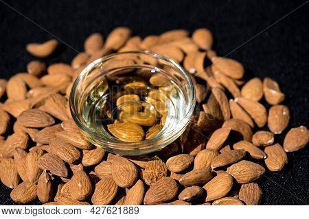 A Pile Of Almonds And A Glas With Almond Oil