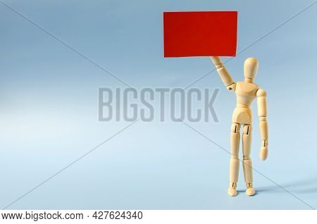 Figure Of A Wooden Man With A Red Poster In His Hand. The Figure Of A Standing Wooden Man On The Lig