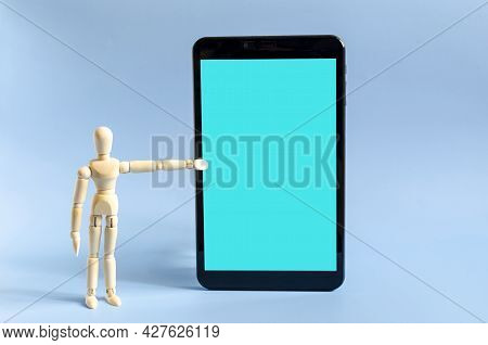 The Figure Of A Wooden Man Pointing At The Tablet Screen With His Hand. The Figure Of A Wooden Man A
