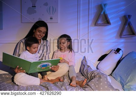 Mother Reading Bedtime Story To Her Children At Home
