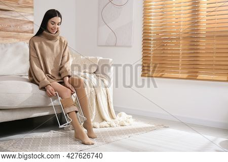 Woman Wearing Compression Tights With Donner In Living Room. Space For Text