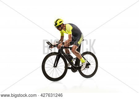 Side View. One Professional Male Cyclist On Road Bike Turning To The Side Isolated Over White Studio