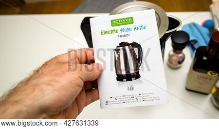 Paris, France - April 24, 2021: Pov Male Hand Holding Instruction Manual Of Activer Electric Water K
