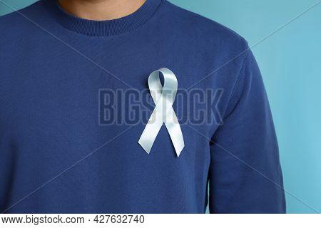 Man With Ribbon On Light Blue Background, Closeup. Urology Cancer Awareness