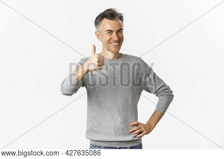 Portrait Of Proud And Happy Middle-aged Man, Smiling Pleased And Showing Thumbs-up, Praise Something