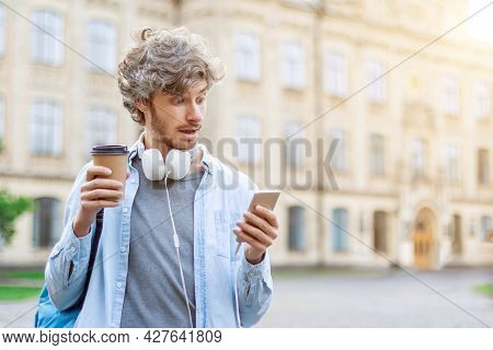 Young Millennial Male Student Is Spending Coffee Break On Chatting In Social Networks And Listening