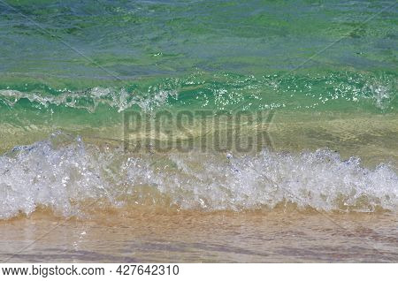 Crystal Clear Blue Sea Water In Various Shades, White Foam And Wave Flooding The Sandy Beach. Fuerte