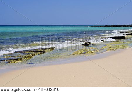 View To The Horizon From The Shore With White Sand And Rocks And Transparent, Sparkling Blue Ocean W