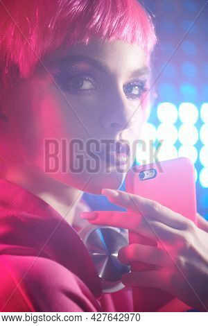 Modern girl with bright glitter makeup and pink hair holding her smartphone in a nightclub. Mixed color light. Disco style.