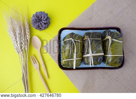 Bundled Boiled Rice. Banana And Sticky Rice Wrapped In Banana Leaves And Black Bean Paste On Dish On