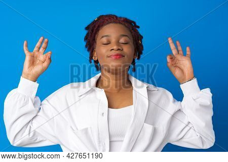 Young Afro Woman Relax With Closed Eyes Against Blue Background