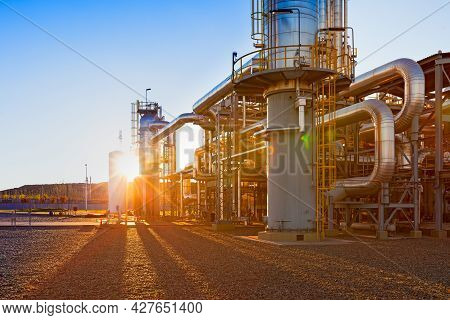View Of A Gas Refinery Plant Illuminated At Sunset
