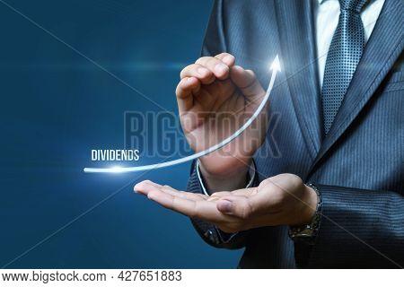 Business Dividend Profit Growth Concept. Businessman Shows An Arrow Of Growing Profits.