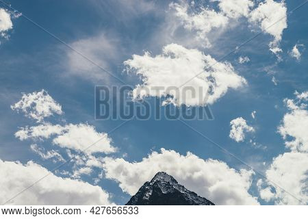 Minimalist Cloudscape With Pointy Peak In Cloudy Blue Sky. Minimal Sky Landscape With Cirrus Clouds