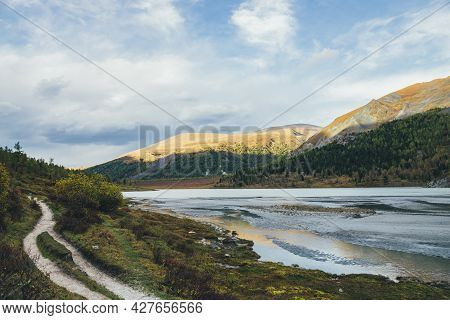 Dramatic Autumn Landscape With Reflection Of Golden Sunlight In Water Stream To Mountain Lake With V