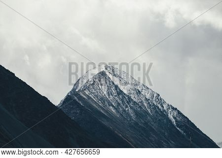 Dark Atmospheric Landscape With High Black Rocky Mountain Top With Snow In Cloudy Sky. Dramatic Moun