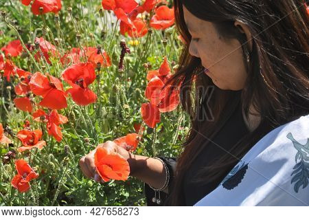 Closeup Shot Of A Nepali Girl Holding And Looking To Red Poppy Flower