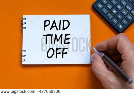 Paid Time Off Symbol. Businessman Writing Words 'paid Time Off' On White Note. Beautiful Orange Back