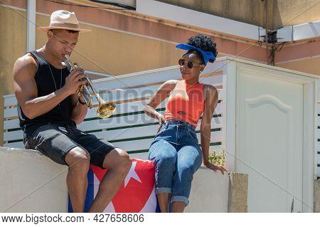 Latina Woman Watching A Latino Man Playing A Trumpet: Selective Focus. Music And Diversity Concept.