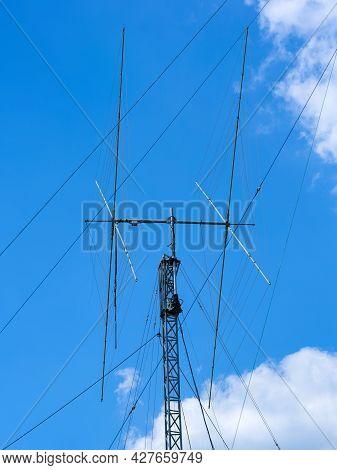 Tall Ham Radio Antenna Against Bluu Cloudy Sky