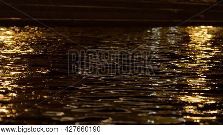 Close Up Of The Surface Of The Water With The Lights Of The Night City. Stock Footage. Rippled Wide