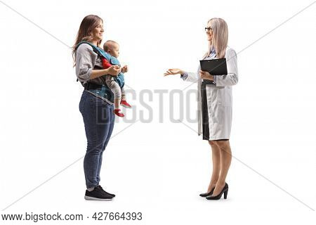 Full length profile shot of a female gynecologist doctor talking to a mother with a baby in a carrier isolated on white background