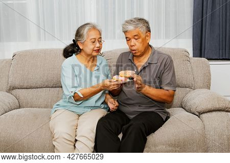 Elderly Asian Couple Sitting On The Sofa Eating Donuts In The Living Room Together : Eating Sweets F