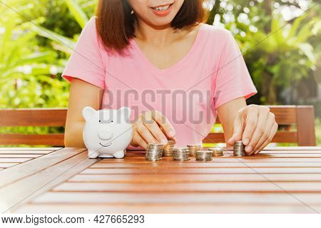 Money Saving Concept : Smile And Happiness Of An Asian Woman Counting The Collected Coins Stacked In