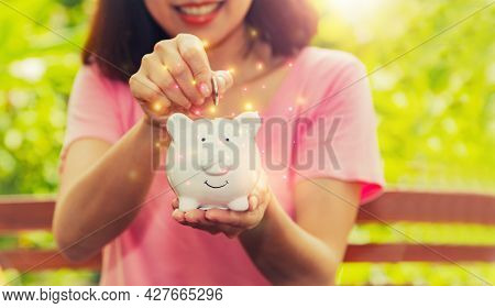 Money Saving Concept : Smile And Happiness Of Asian Woman Put A Coin In Her Home's White Piggy Bank