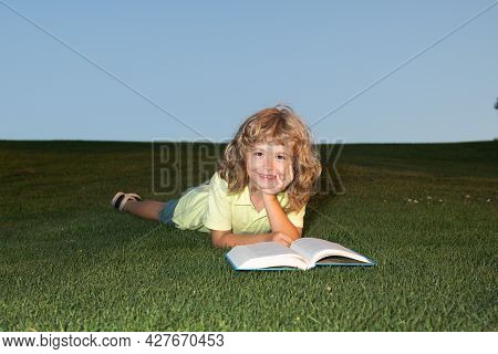 A Young Blonde Boy Is Lying On The Green Grass Outdoors Reading A White Book In Summer. Smart Child