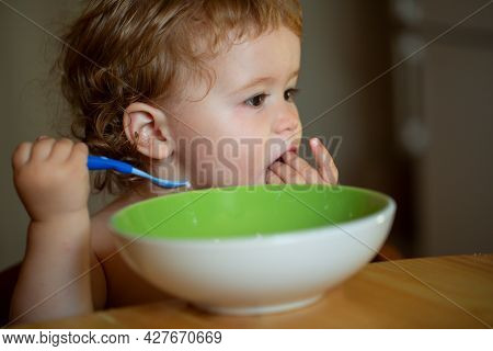 Funny Baby Eating Food Himself With A Spoon On Kitchen.