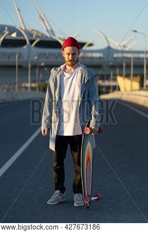 Hipster Skateboarder Man Holding Trendy Longboard Skate On City Street. Trendy Urban Male Lifestyle.