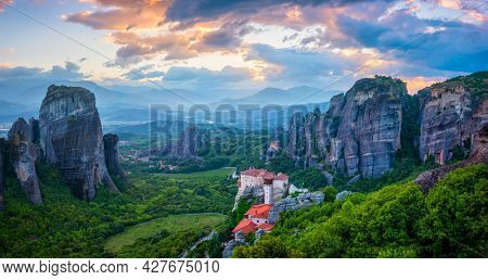 Sunset sky and monastery of Rousanou and Monastery of St. Nicholas Anapavsa in famous greek tourist destination Meteora in Greece with sun rays and lens flare