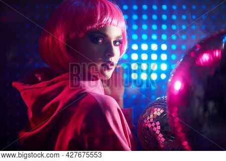 DJ girl. Attractive girl with bright glitter make-up and pink hair poses with disco ball and headphones in neon light. Night party. Disco girl.