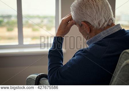 Sad and depressed old man sitting on armchair in living room feeling hurt and lonely. Frustrated senior sitting on sofa at nursing home with head leaning on his hand while looking through the window.