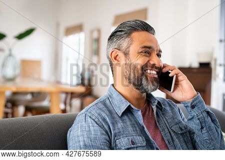 Indian mature man talking over smartphone while sitting on couch. Close up face of middle eastern man smiling and discussing on smart phone. Mid adult guy sitting in living room using cellphone.