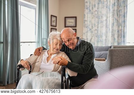 Romantic senior man embracing woman sitting on wheelchair at nursing home. Elderly couple in love embracing with eyes closed and deep respect for each other. Lovely man at care centre during a visit.